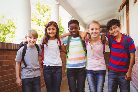 Foto de Portrait of smiling little school kids in school corridor - Imagen libre de derechos