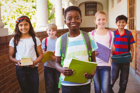 Photo pour Portrait of smiling little school kids in school corridor - image libre de droit