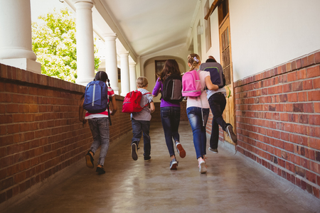 Photo for Full length rear view of school kids running in school corridor - Royalty Free Image