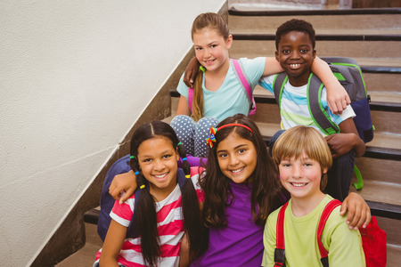Foto de Portrait of school kids sitting on stairs in the school - Imagen libre de derechos