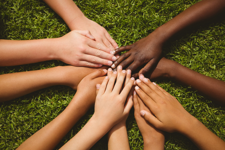 Photo for Close up of children keeping hands together over grass - Royalty Free Image