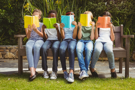 Photo for Children sitting in row and reading books at the park - Royalty Free Image
