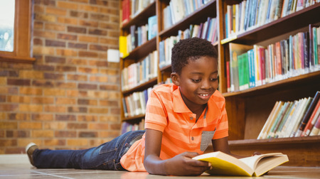 Photo pour Cute little boy reading book in the library - image libre de droit