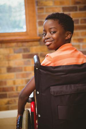 Foto de Portrait of cute little boy sitting in wheelchair in school - Imagen libre de derechos