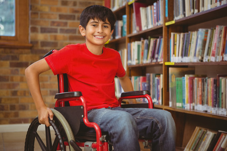 Foto de Portrait of little boy sitting in wheelchair at the library - Imagen libre de derechos