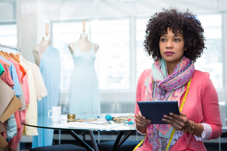 Photo pour Attractive female fashion designer using digital tablet - image libre de droit
