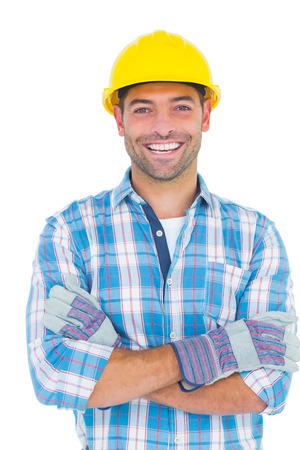 Foto de Portrait of smiling manual worker with arms crossed on white background - Imagen libre de derechos
