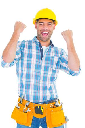 Foto de Portrait of excited manual worker clenching fists on white background - Imagen libre de derechos