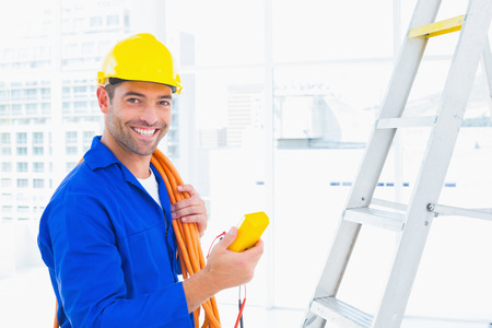 Foto de Portrait of smiling male electrician holding multimeter in bright office - Imagen libre de derechos