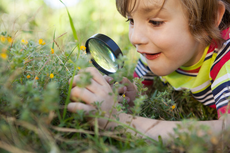Photo for Happy little boy looking through magnifying glass on a sunny day - Royalty Free Image
