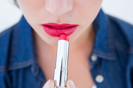 Photo pour Woman putting red lipstick on white background - image libre de droit