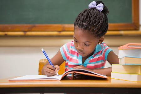 Foto de Cute pupils writing at desk in classroom at the elementary school - Imagen libre de derechos