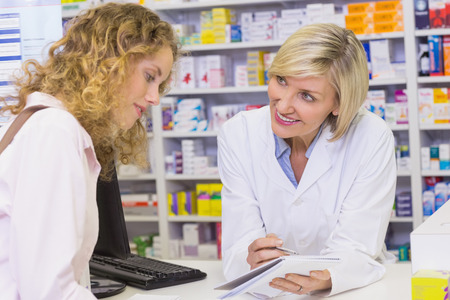 Photo for Pharmacist showing prescription to a customer at pharmacy - Royalty Free Image