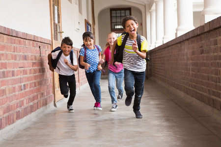 Photo pour Cute pupils running down the hall at the elementary school - image libre de droit