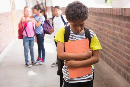 Foto de Pupils friends teasing a pupil alone in elementary school - Imagen libre de derechos