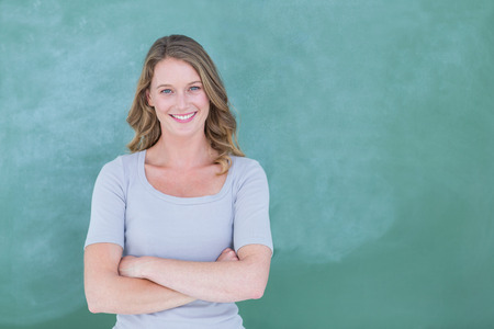 Photo pour Smiling teacher standing in front of blackboard in classroom - image libre de droit