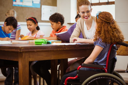 Foto de Teacher helping a disabled pupil at the elementary school - Imagen libre de derechos