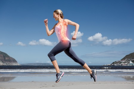 Foto de Digital composite of Highlighted back bones of jogging woman on beach - Imagen libre de derechos
