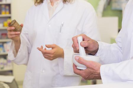 Foto de Team of pharmacists holding medicines and mortar at hospital pharmacy - Imagen libre de derechos