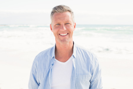 Photo for Handsome man smiling at camera at the beach - Royalty Free Image