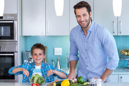 Photo pour Happy family preparing lunch together at home in the kitchen - image libre de droit