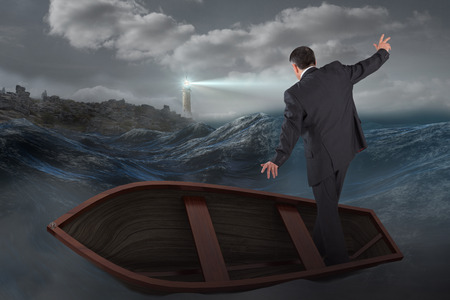 Foto de Businessman balancing in boat against stormy sea with lighthouse - Imagen libre de derechos