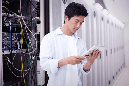 Foto de Male looking at his tablet computer against data center - Imagen libre de derechos