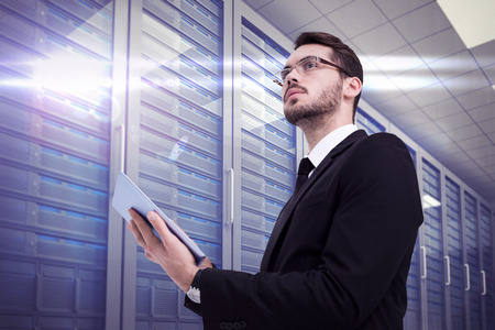Foto de Businessman looking away while using tablet against server room - Imagen libre de derechos