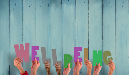 Photo for Hands holding up well being against wooden planks - Royalty Free Image