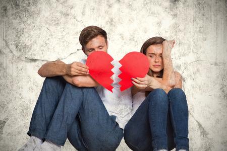 Foto de Young couple holding broken heart against grey background - Imagen libre de derechos