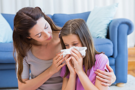 Foto de Mother helping daughter blow her nose at home in the living room - Imagen libre de derechos