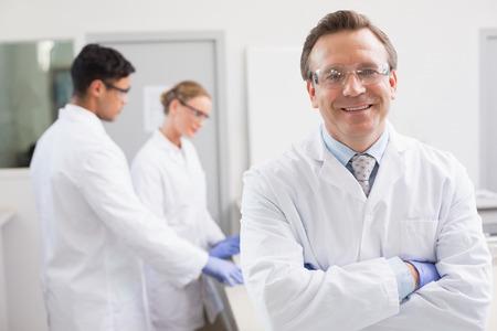 Foto de Smiling scientist looking at camera while colleagues working behind in laboratory - Imagen libre de derechos