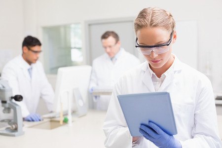Foto de Scientist using tablet while colleagues working behind in laboratory - Imagen libre de derechos