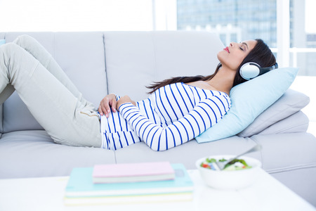 Photo pour Smiling beautiful brunette relaxing on the couch and listening music in the living room - image libre de droit