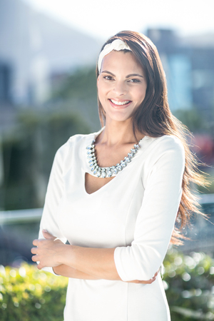 Photo for Gorgeous woman smiling at camera with arms crossed outside - Royalty Free Image