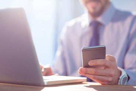 Foto de Businessman using laptop at desk shot in studio - Imagen libre de derechos