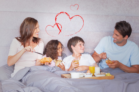 Family having breakfast in bed against heart