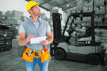 Foto de Manual worker looking away while writing on clipboard against warehouse worker loading up pallet - Imagen libre de derechos