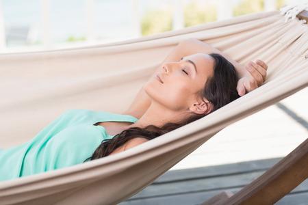 Photo pour Pretty brunette relaxing on a hammock in patio - image libre de droit