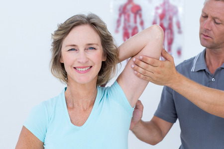 Photo for Woman stretching her arms with her doctor in medical office - Royalty Free Image