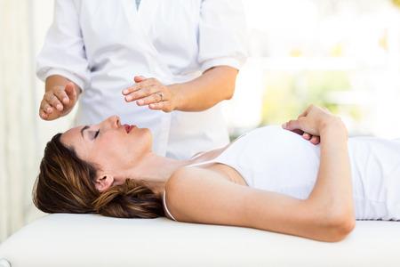 Photo pour Calm woman receiving reiki treatment in the health spa - image libre de droit