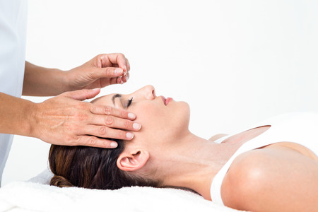 Photo pour Relaxed woman receiving an acupuncture treatment in a health spa - image libre de droit