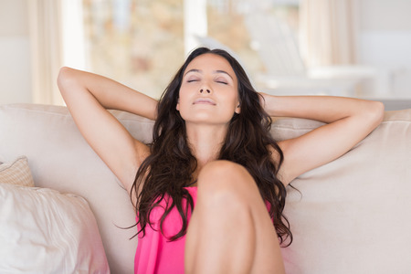 Photo pour Pretty brunette relaxing on the couch at home in the living room - image libre de droit