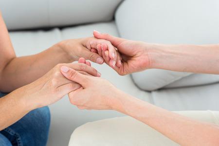 Foto de Therapist holding her patients hands on white background - Imagen libre de derechos