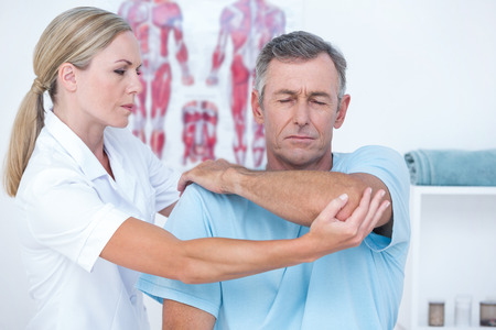 Photo pour Doctor stretching a man arm in medical office - image libre de droit