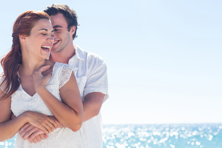 Foto de Happy couple hugging and laughing together at the beach - Imagen libre de derechos