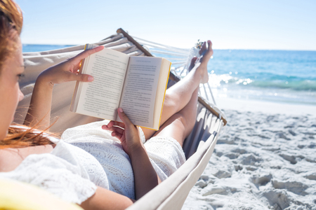 Photo pour Brunette reading a book while relaxing in the hammock at the beach - image libre de droit