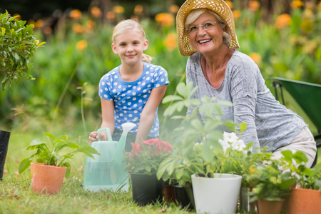 Foto de Happy grandmother with her granddaughter gardening on a sunny day - Imagen libre de derechos