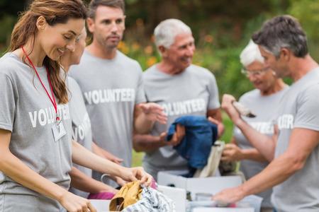 Foto de Happy volunteer looking at donation box on a sunny day - Imagen libre de derechos
