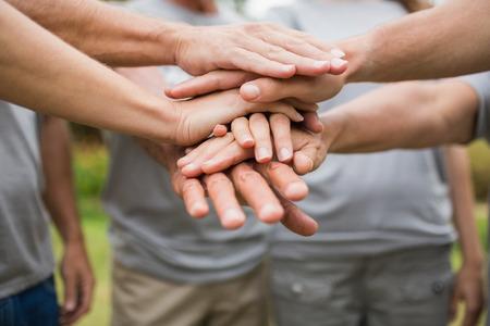 Foto de Happy volunteer family putting their hands together on a sunny day - Imagen libre de derechos